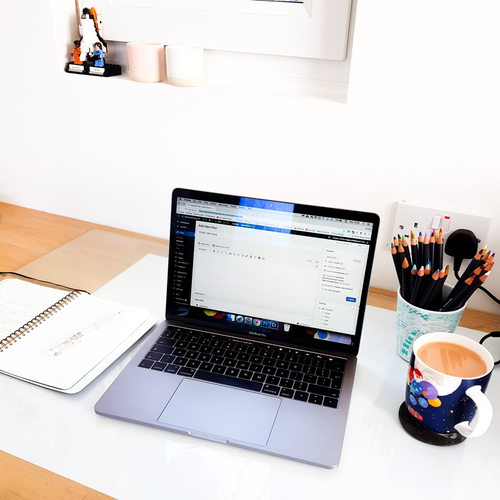 image of desk with laptop and notebook on surface self-hosting wordpress
